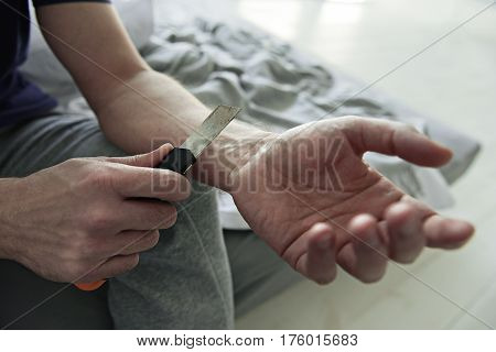 Upset male person is committing suicide. He is holding paper-cutter. Focus on his hand. Close-up