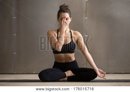 Young attractive sporty yogi woman practicing yoga, sitting in Sukhasana pose, Alternate Nostril Breathing, nadi shodhana pranayama exercise, working out, cool urban style, full length, grey studio