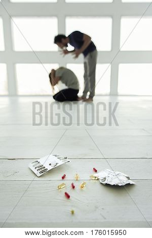 Domestic violence. Focus at different pills and its packages. Irritated man is shouting at his wife on background