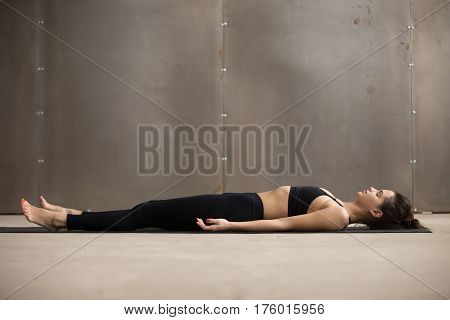 Young attractive woman practicing yoga, lying in Dead Body, Savasana exercise, Corpse pose, working out, wearing black sportswear, cool urban style, full length, grey studio background