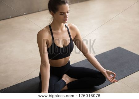 Young smiling attractive yogi woman practicing yoga, sitting in Sukhasana exercise, Easy Seat pose with mudra, working out, wearing black sportswear, cool urban style, grey studio background