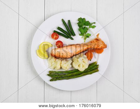 Grilled salmon with vegetables on white old wooden rustic table. Top view