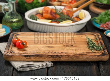Cutting board with napkin on a dark wooden table with a free place for you