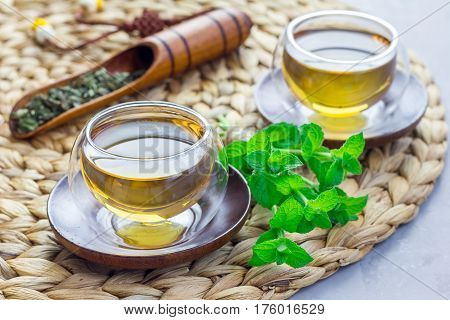 Healthy herbal mint tea in oriental glass cup with fresh peppermint and tea scoop on background horizontal
