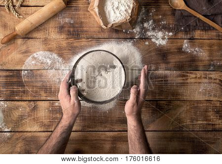 Man sifted flour on the wooden table top view
