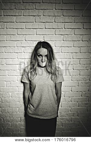 Frustrated female person with taped mouth looking at camera with despair. She standing nearby wall. Black-and-white portrait