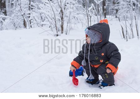 Children's winter games outdoors. The image of a child plays with snow in winter park. and playing with a large colourful toy car. Little Baby Playing with Snow in Winter Outdoors