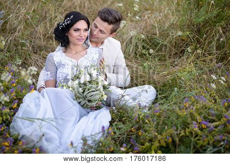 Young couple in love outdoor. Elegant bride and groom posing together outdoors on a wedding day. bride and groom in the Park. young couple in the woods. young couple in the grass. couple walking