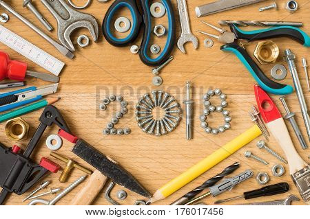 Happy new year 2018 composition with screws nails bolts dowels and tools on wooden background. New year. New year background.