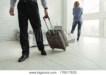 Man is holding big case and leaving room. Upset woman standing near bed