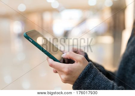 Woman sending sms on mobile phone in shopping mall