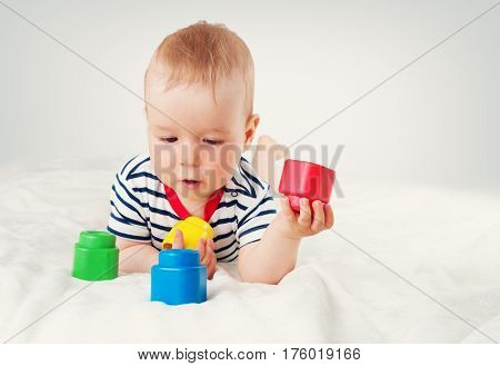 Nine month old baby lying in the bed on white blanket. Cute boy playing with cubes