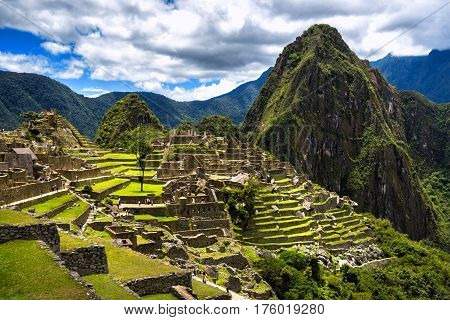 View of the Lost Incan City of Machu Picchu near Cusco Peru. Machu Picchu is a Peruvian Historical Sanctuary. People can be seen on foreground.