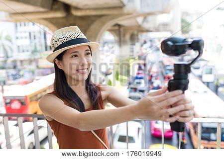 Woman using video stabilizer to take video at bangkok city