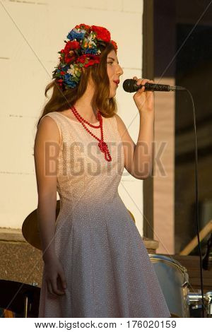 MARGANETS, UKRAINE - JUNE 26, 2016: Young unknown female artist singing while giving concert in Marganets on National Youth Day