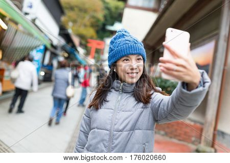 Woman taking selfie by mobile phone in Kamakura city