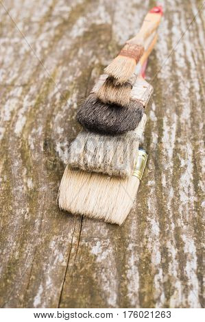 Set of old brush for coloring the walls Brush painting wooden furniture close up Paintbrush on wood background Vintage old painting brushes. Team work concept.