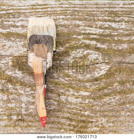 Old painting brushes. Used brushes for painting lie on the old wooden rustic table. Used brushes on wooden background