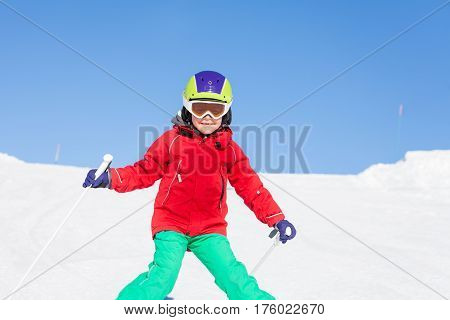 Happy skier boy walking down the hill in mountains during winter holiday
