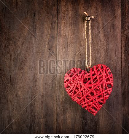 Valentines Day red wicker heart on vintage wooden background