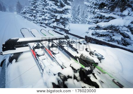 Car driving on the snowcapped road with skis on the roof rails in the evening