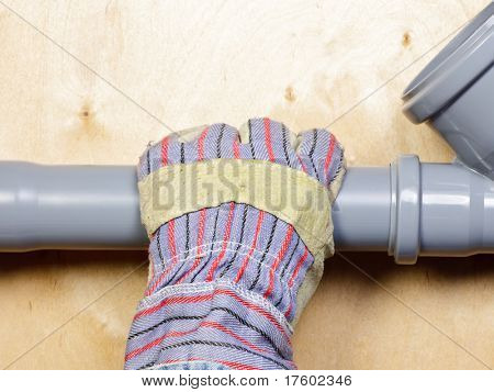 Plumber's hand wearing protective glove with pvc sewage pipes