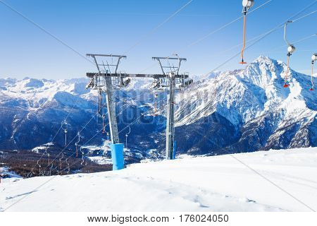 Ski resort with aerial ropeway and button lifts in the midst of beautiful snow-covered mountains
