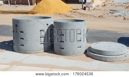Two concrete soakwells with covers on the construction site before installation