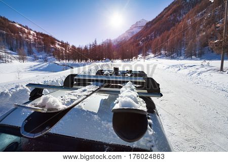 Beautiful mountain scene with snowcapped skis fastened on car roof rails in the foreground