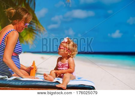 sun protection -mother applying sunblock cream on little daughter