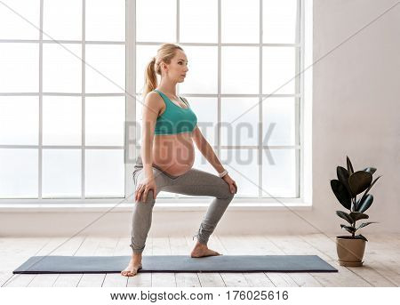 Staying fit for her baby. Full length portrait of happy young future mother wearing workout clothes and doing gymnastic at home