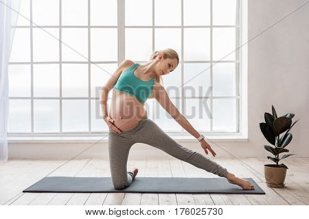 Joyful yoga. Full length portrait of happy pregnant woman exercising and stretching leg on mat at home with window on background