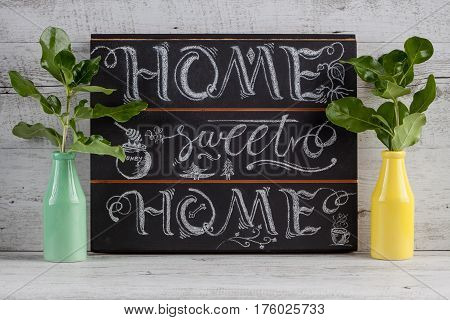 Hand lettering calligraphy sign drawn with chalk. Lettered quote 'Home sweet home' to use as decoration or in greeting cards