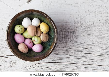 Sugar Coated Speckled Easter Eggs In Ceramic Bowl On White Rustic Wooden Table. Top View With Copy S