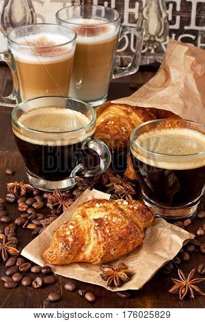 Fresh croissants  and coffee cups for breakfast on wooden  vintage table