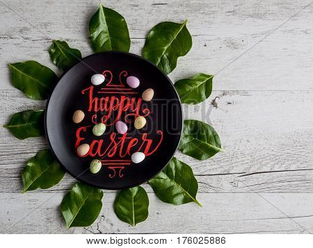 Happy Easter Hand Lettering Written In Red On Black Plate Decorated With Sugar-coated Speckled Choco