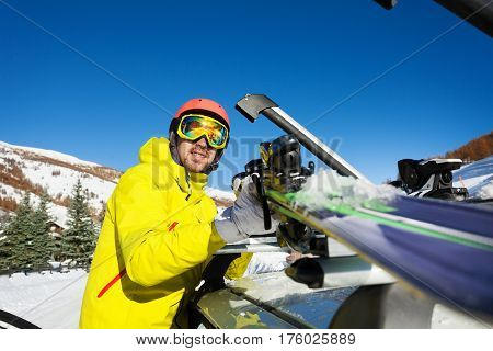 Active man fastening skis on the roof of car at sunny day