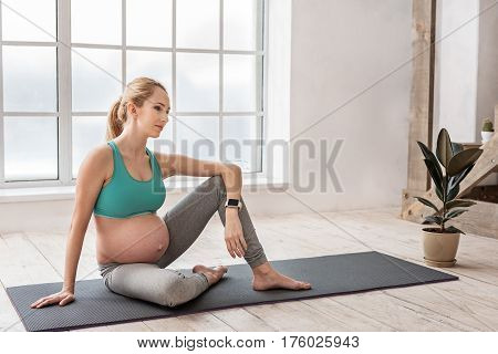 Calm and tranquility for mom and baby. Full length portrait of smiling young pregnant woman sitting on yoga mat indoors while relaxing after exercise