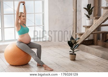 I just love my big belly. Full length portrait of smiling healthy future mother training with fitness ball while sitting on it and raising her hands up