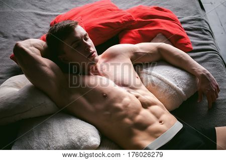 Studio Portrait Young Sexy Men Bodybuilder Athlete, With A Bare Torso, Lies On A Bed In Pillows In U
