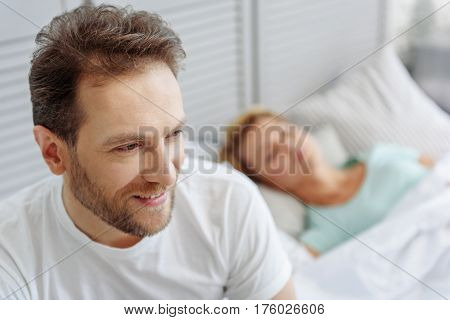 Portrait of joyful husband waking up in the morning with happiness. He is sitting near his sleeping wife and smiling