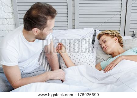 Happy man is watching his wife sleeping with pleasure. He is sitting on bed in nightwear and relaxing