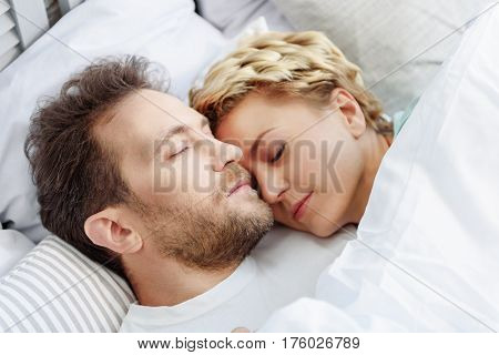 Peaceful loving married couple is sleeping together on bed