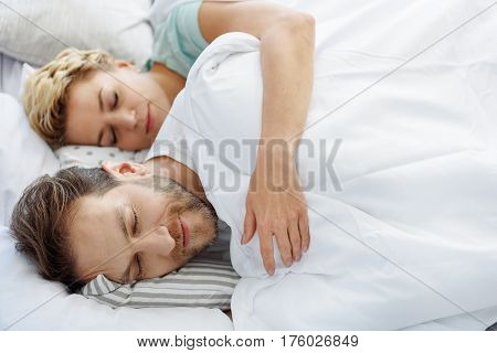 Cute middle-aged husband and wife are napping together in bedroom. Woman is embracing smiling man with love