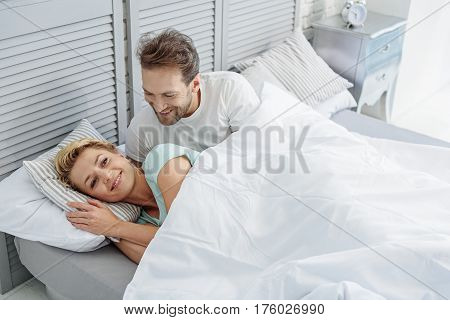 Good morning, my love. Joyful married couple is waking up in the morning together. Husband is smiling and looking at lady with happiness
