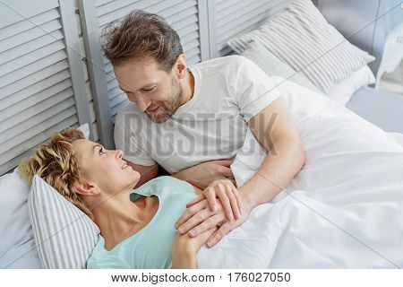 I love you. Pretty married couple is lying on bed and looking at each other with affection. They are holding hands and smiling