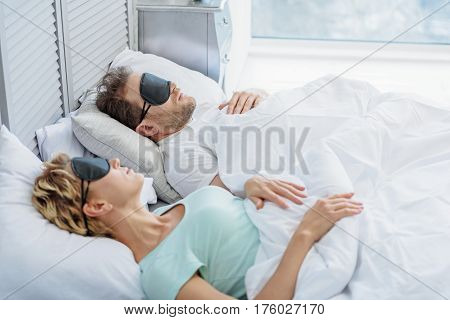 Calm man and woman are enjoying dreams on bed. They are lying with relaxation