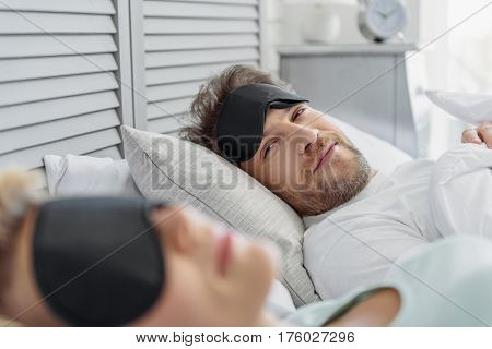 You are woman of my dream. Happy man is looking his sleeping wife with admiration. He is lying on bed with sleep mask