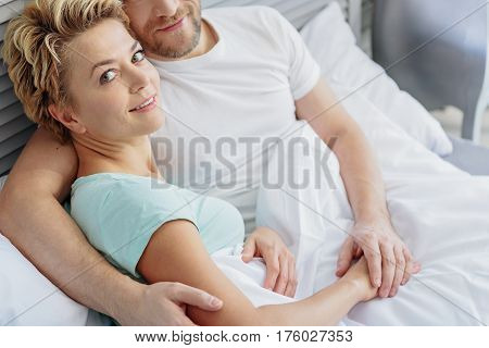 I like spending time with my husband. Cheerful middle-aged woman is looking at camera and smiling. Man is sitting on bed and embracing her with love