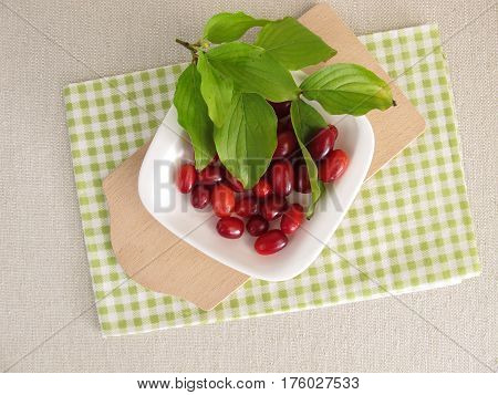 Ripe raw cornelian cherries with leaves in bowl